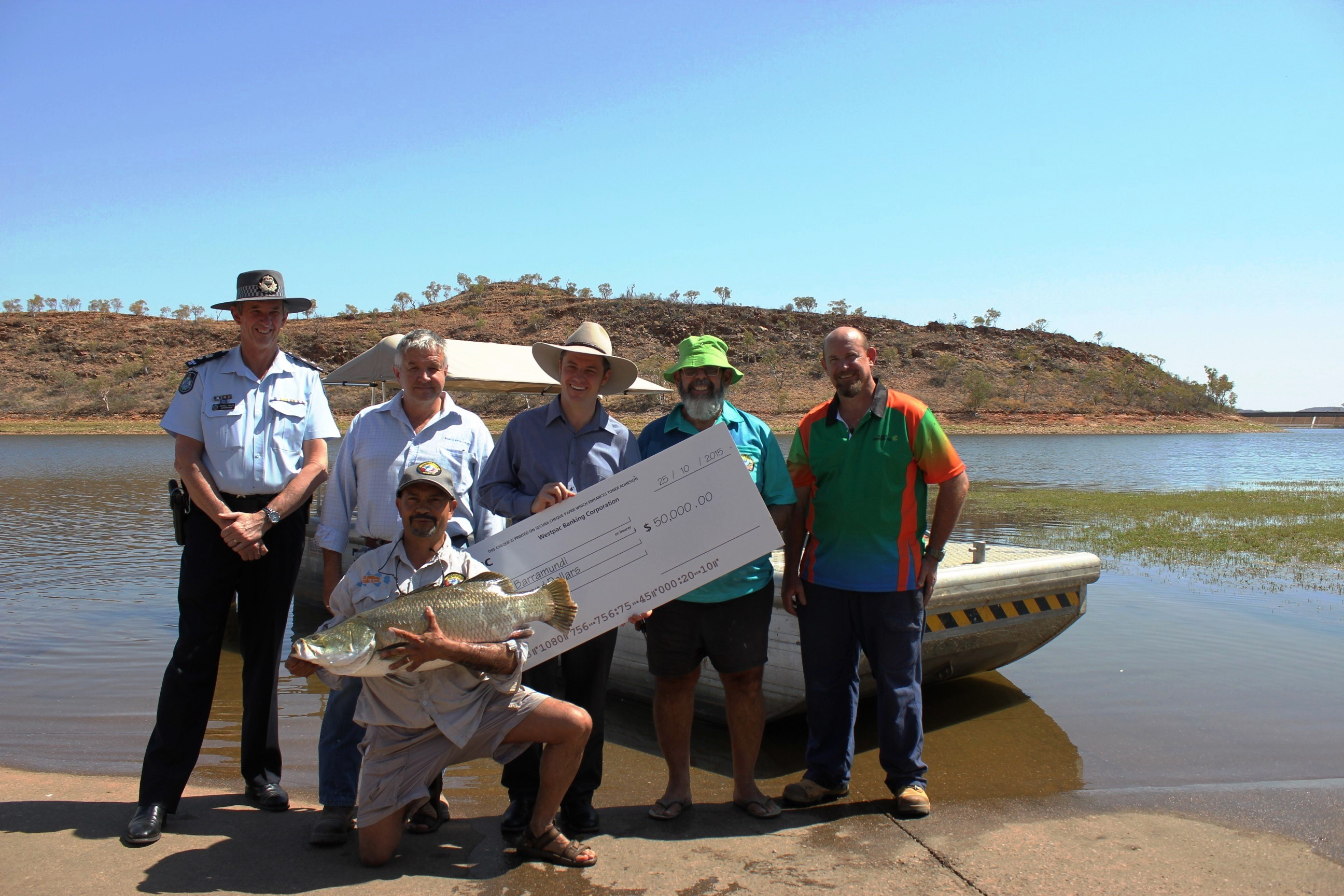L-R Russell Miller- Superintendent District Officer Mount Isa Police, Cr Brett Peterson- Deputy Mayor Mount Isa City Council, Stephen Farrelly Chief Executive Mount Isa Water Board, Steve Farnsworth- Co-Event Manager Lake Moondarra Fishing Classic, Dave Clancy- Director Clancy Corporation and George Fortune Co-Event Manager Lake Moondarra Fishing Classic (inset) with $50,000 Mount Isa Water Board Tagged Barra 'Fat Albert' prior to release at Lake Moondarra.