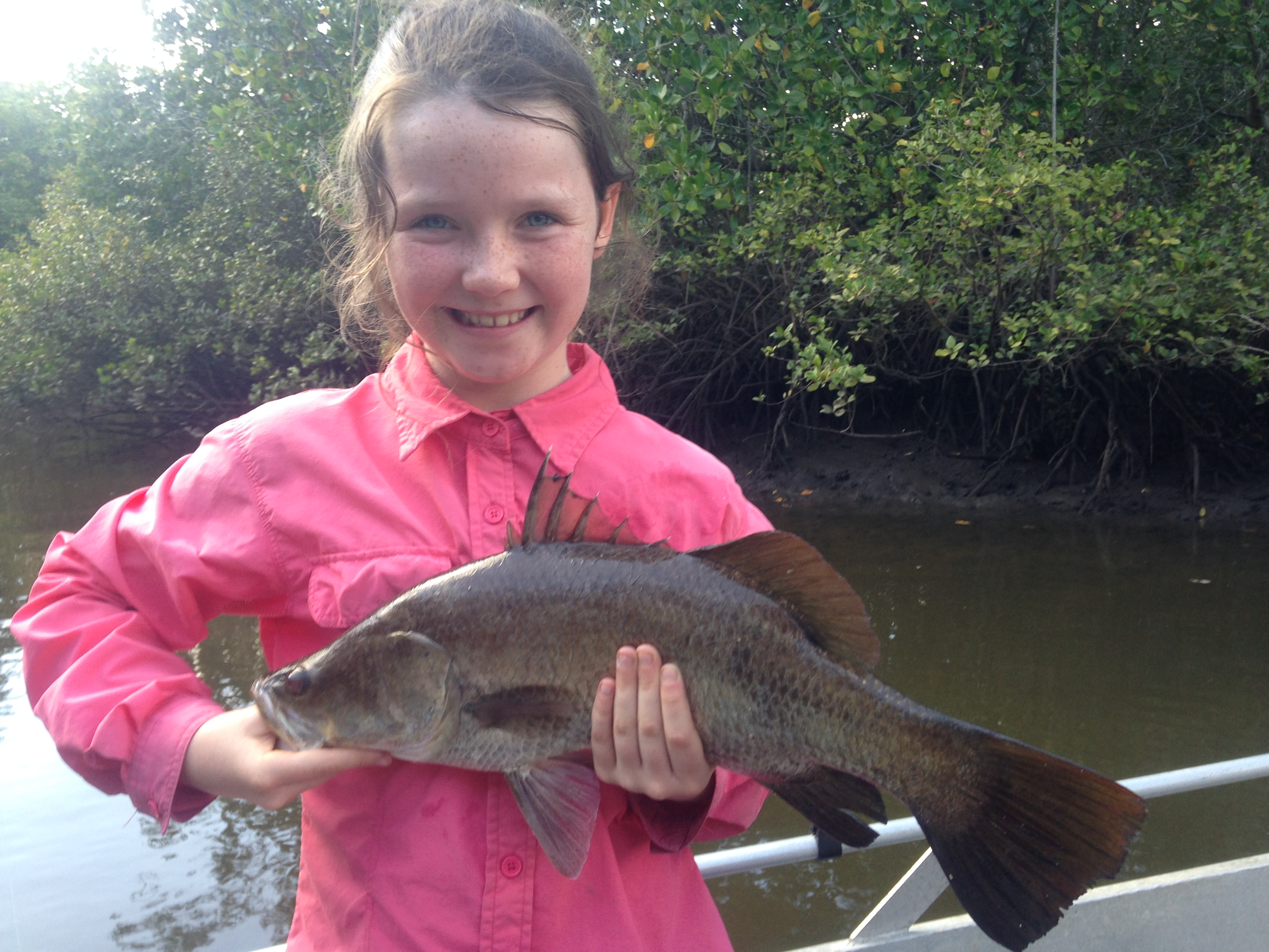 The author's 10-year-old sister with her first lure-caught barra.