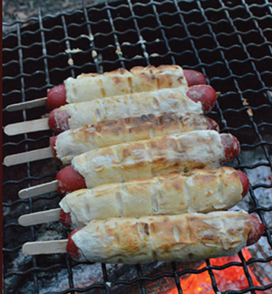 Cooking hot dogs over the fire gives them a nice smoky flavour and they are delicious served with your favourite sauce. Cook over a slow bed of coals to avoid burning.