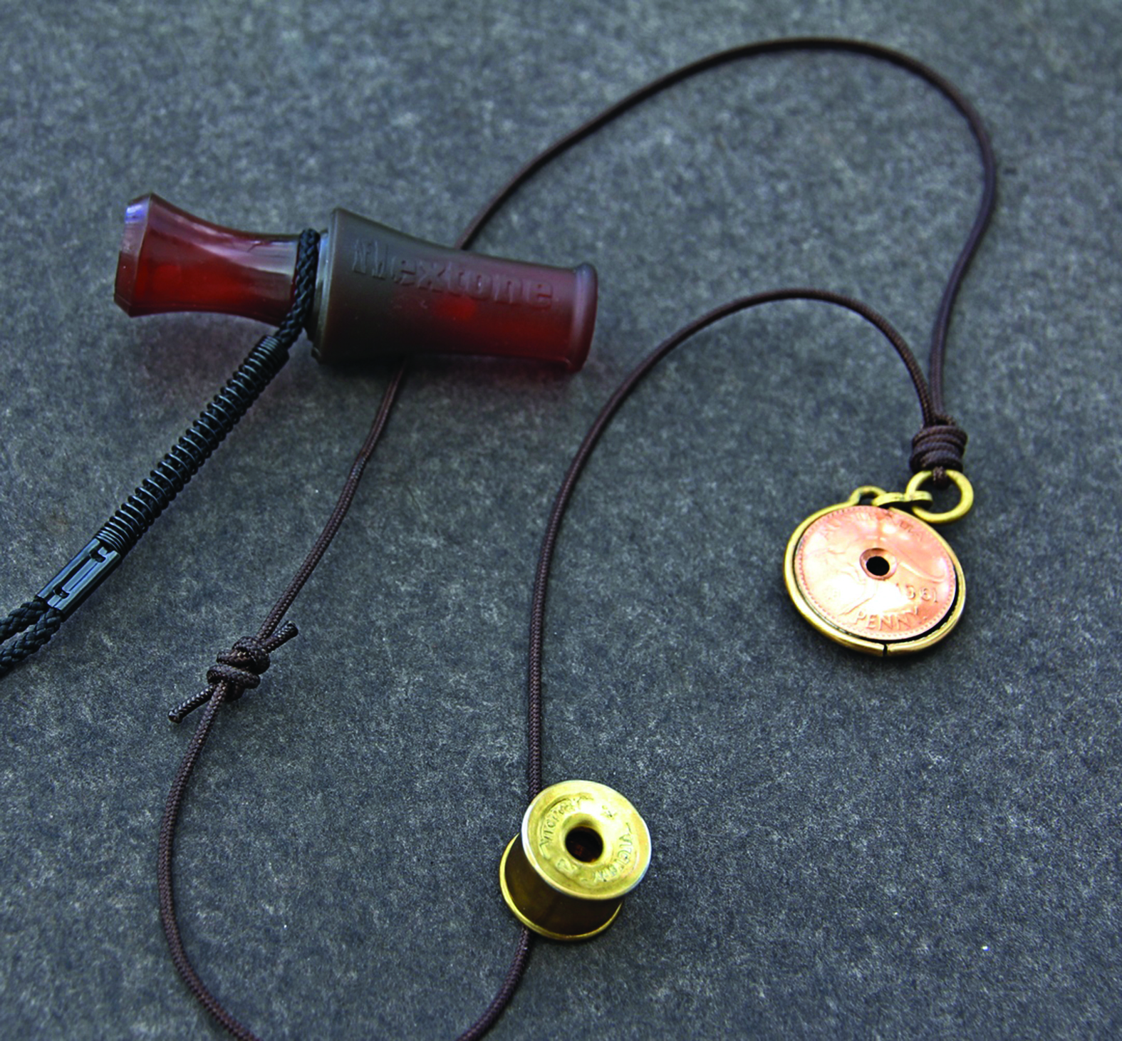 The author's favourite fox whistles. Closest to the camera is a design made from the brass ends of two 12-gauge shotgun shells. The other metal whistle is of a more traditional shape, but was fashioned from two old Australian pennies. The upper whistle is a Flextone Dying Rabbit call made of rubber and plastic. It doesn't produce the same high-pitched squeak of most fox whistles but does bring them in.